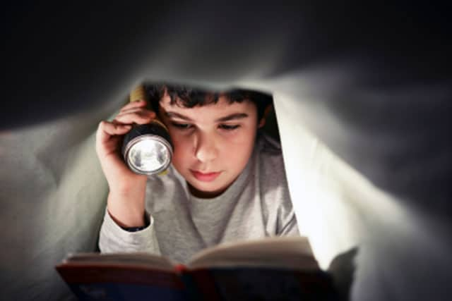 Kid-Reading-Under-Covers